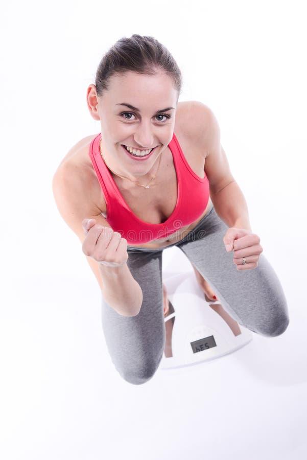 Mooie gelukkige jonge vrouw met het verlies van het het succesgewicht van de gewichtsschaal royalty-vrije stock foto's
