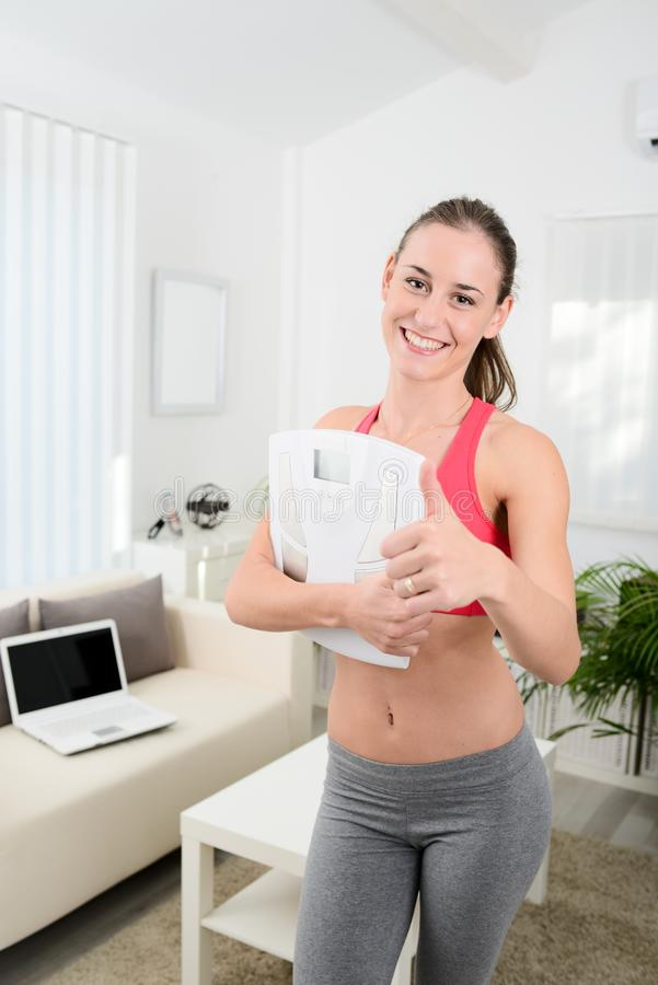 Mooie gelukkige jonge vrouw met het verlies van het het succesgewicht van de gewichtsschaal stock foto's
