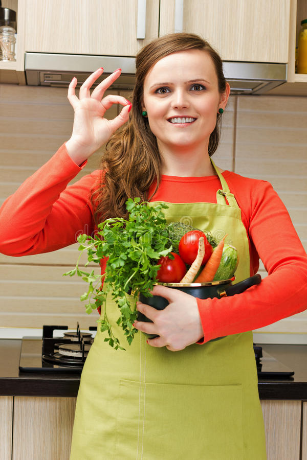 Mooie gelukkige jonge vrouw met schort holdin een pot en het maken van o royalty-vrije stock afbeeldingen