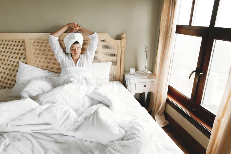 Mooie gelukkige jonge vrouwenontwaken in bed met witte bladen in hotelruimte of huisslaapkamer Meisje in het witte handdoek ontsp royalty-vrije stock afbeelding
