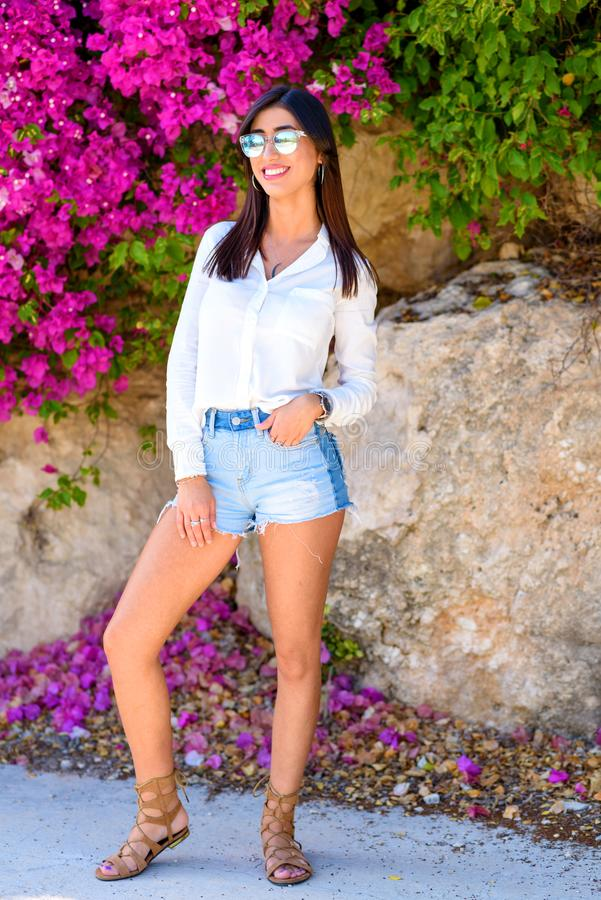 Mooie gelukkige manier jonge vrouw die zich op een kleurrijke natuurlijke achtergrond van heldere roze bloemen bevinden royalty-vrije stock afbeeldingen