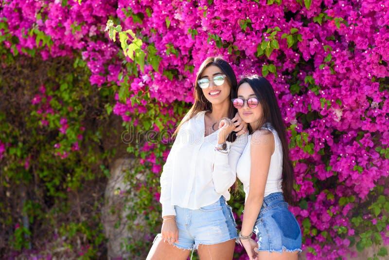 Mooie gelukkige manier jonge vrouwen die zich op een kleurrijke natuurlijke achtergrond van heldere roze bloemen bevinden royalty-vrije stock foto