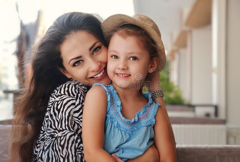 Mooie gelukkige moeder die haar het joying het glimlachen dochterindoo koesteren royalty-vrije stock fotografie