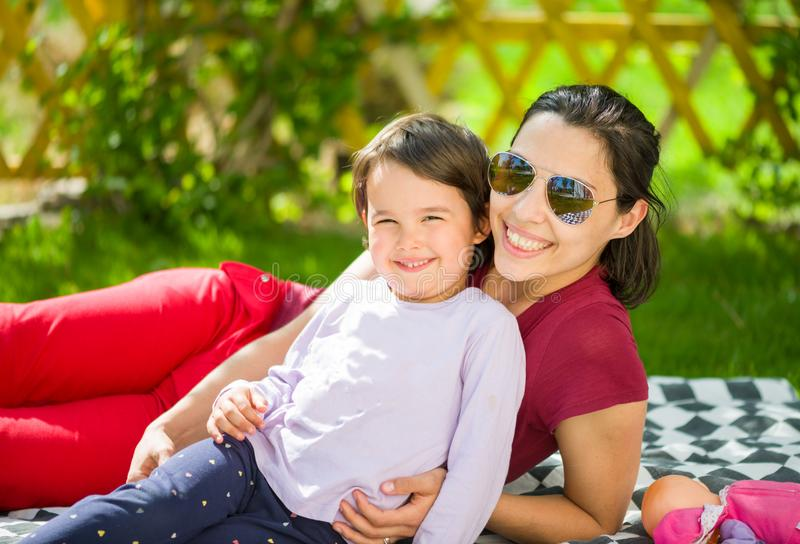 Mooie gelukkige moeder die op gras met haar meisje liggen royalty-vrije stock afbeeldingen