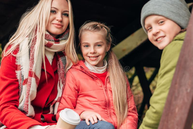 mooie gelukkige moeder met kinderen die bij camera glimlachen terwijl het rusten royalty-vrije stock fotografie