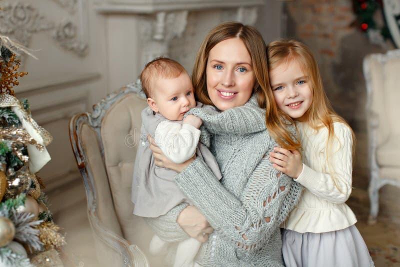 Mooie gelukkige moeder met kleine dochters die op de rug zitten royalty-vrije stock foto