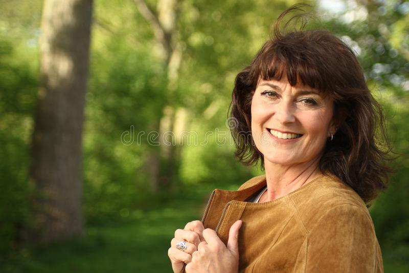Mooie gelukkige rijpe Kaukasische vrouw buiten in het park stock afbeelding