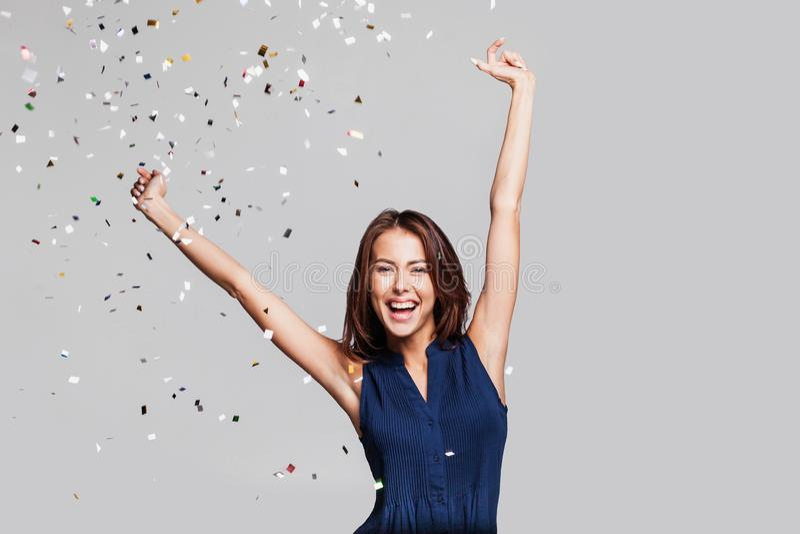 Mooie gelukkige vrouw bij vieringspartij met confettien die overal op haar vallen Verjaardag of Nieuwjaarvooravond het vieren con royalty-vrije stock foto's