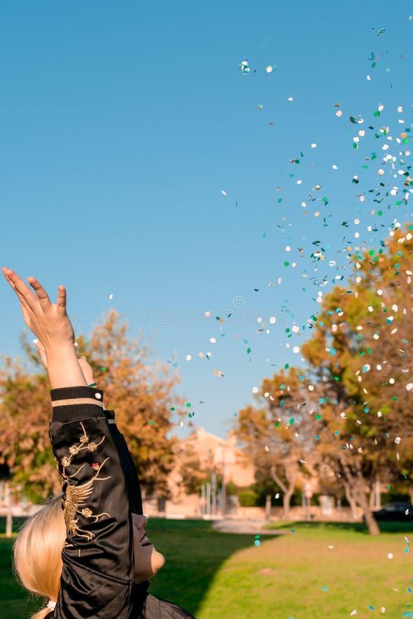 Mooie gelukkige vrouw bij vieringspartij met confettien die overal op haar vallen stock foto