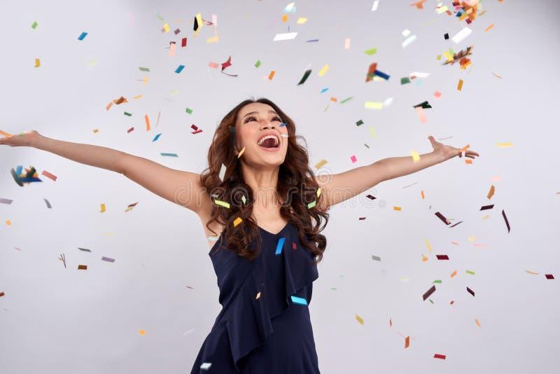 Mooie gelukkige vrouw bij vieringspartij met confettien het vallen royalty-vrije stock afbeelding