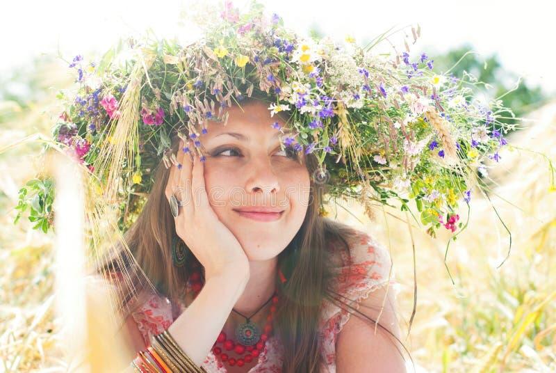 Mooie gelukkige vrouw in bloemkroon in de zomer stock foto
