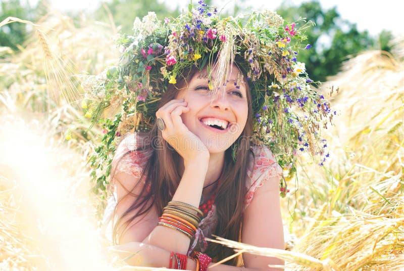 Mooie gelukkige vrouw in bloemkroon in de zomer royalty-vrije stock fotografie