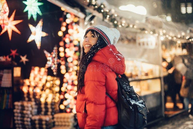 Mooie gelukkige vrouw die een heden op de markt van de Kerstmisstad zoeken tijdens sneeuwonweer royalty-vrije stock foto's