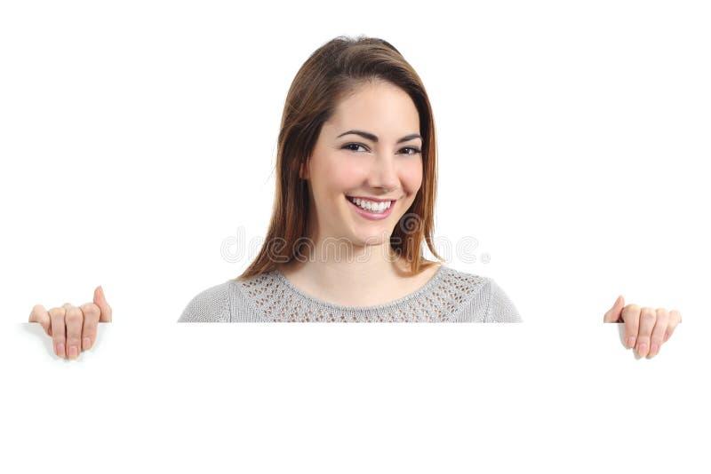 Mooie gelukkige vrouw die en een leeg aanplakbiljet glimlachen houden stock fotografie