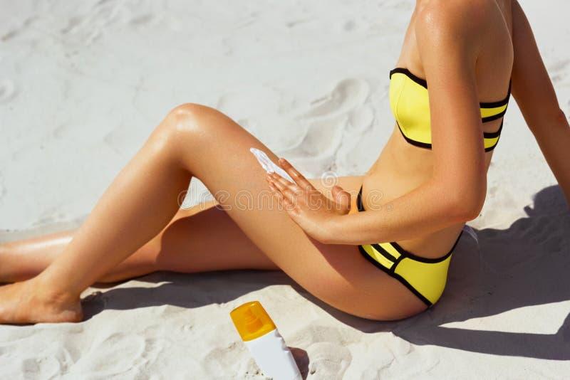 Mooie gelukkige vrouw die in gele bikini de room van het zonblok op gelooid lichaam toepast royalty-vrije stock fotografie