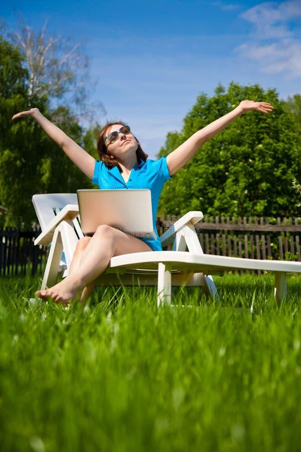 Mooie gelukkige vrouw die met laptop van de zon genieten stock afbeelding