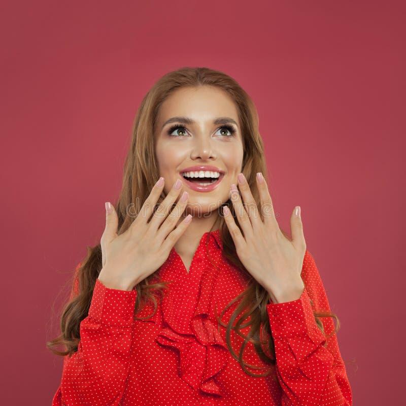 Mooie gelukkige vrouw die omhoog op kleurrijke heldere roze achtergrond kijken Perfect meisje het lachen portret Positieve emotie stock foto