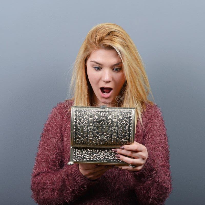 Mooie gelukkige vrouw die uitstekende doos openen tegen grijze achtergrond royalty-vrije stock afbeelding