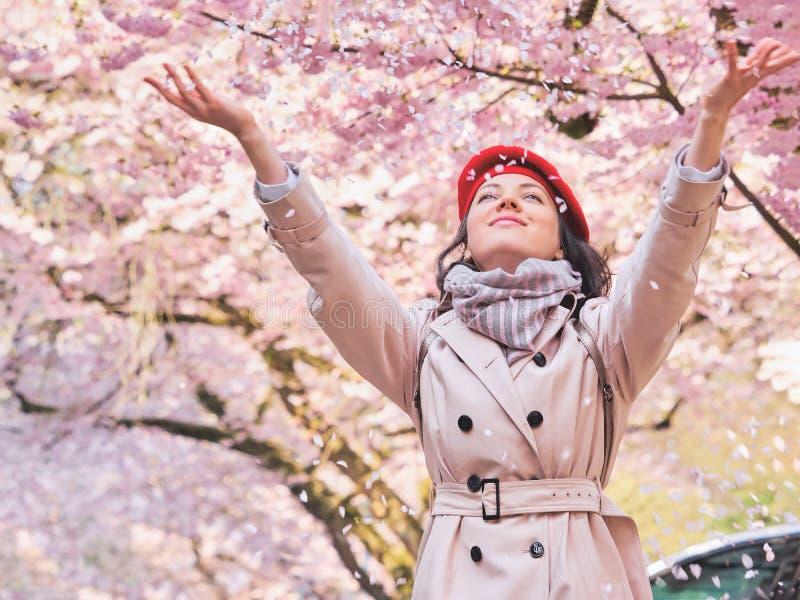 Mooie gelukkige vrouw die van geur in een bloeiende de lentetuin genieten royalty-vrije stock foto's