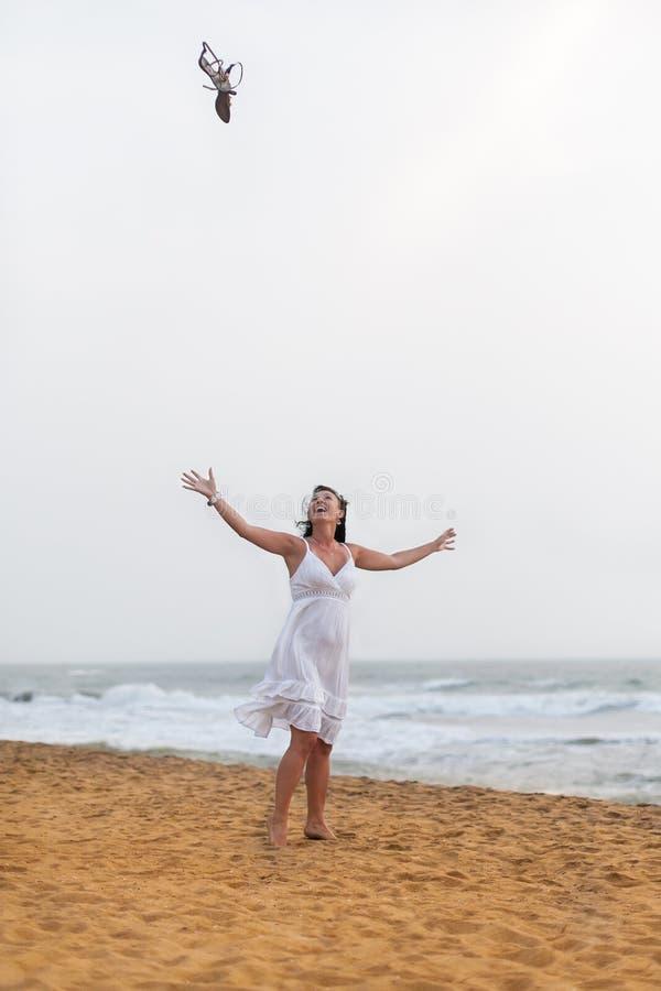 Mooie gelukkige vrouw die in witte kleding op het zandige strand lopen, die zijn sandals werpen Reis en de zomerconcept stock afbeelding