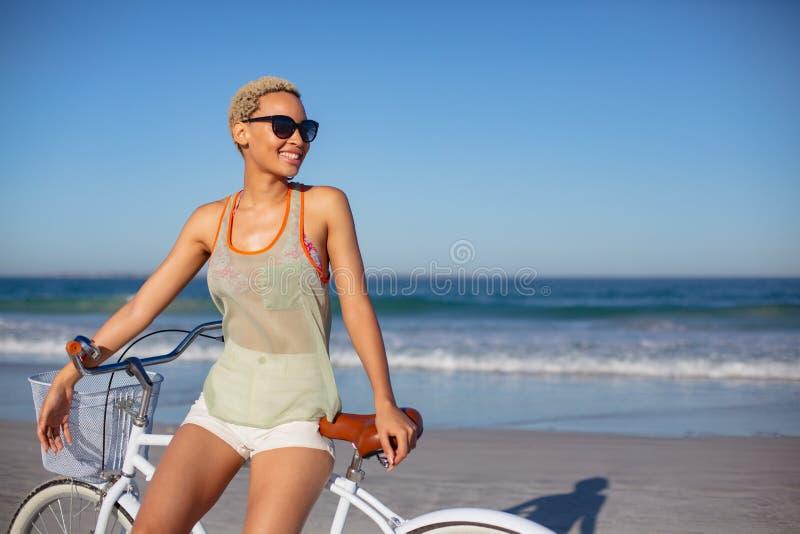 Mooie gelukkige vrouw die in zonnebril op fiets bij strand in de zonneschijn zitten stock fotografie