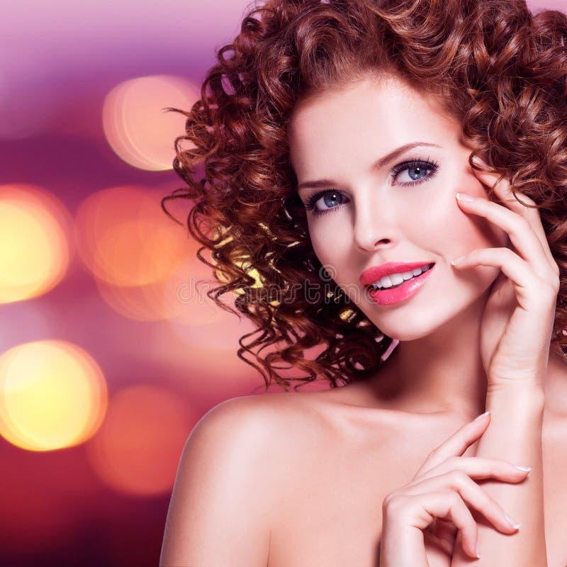 Mooie gelukkige vrouw met donkerbruin krullend haar royalty-vrije stock foto