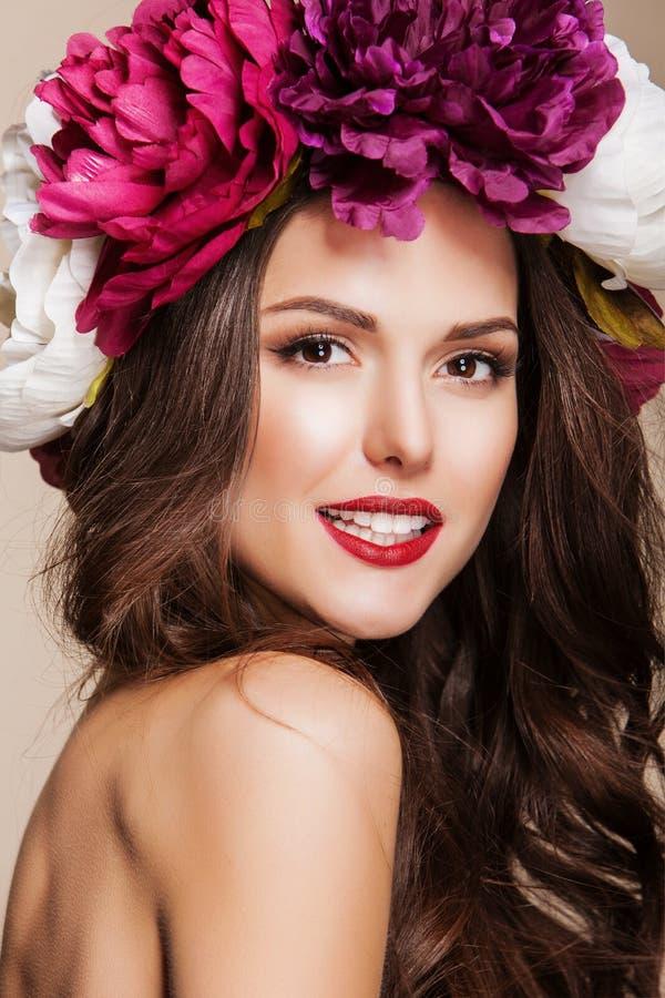 Mooie gelukkige vrouw met heldere bloemen op haar hoofd en rode lippen royalty-vrije stock afbeelding