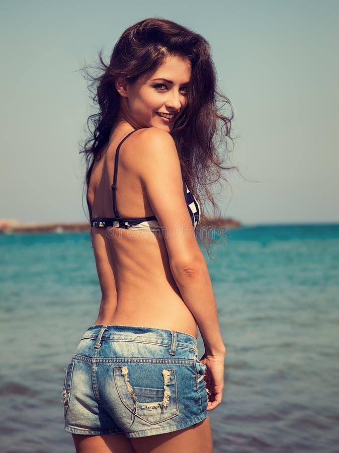 Mooie gelukkige vrouw in van de jeansborrels en bikini het stellen op blauw stock afbeeldingen