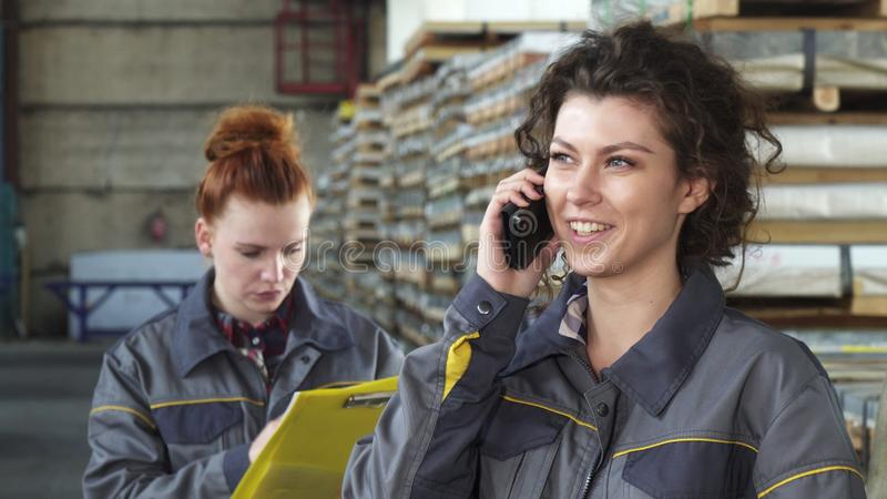 Mooie gelukkige vrouwelijke fabrieksarbeider die op de telefoon spreken stock foto's