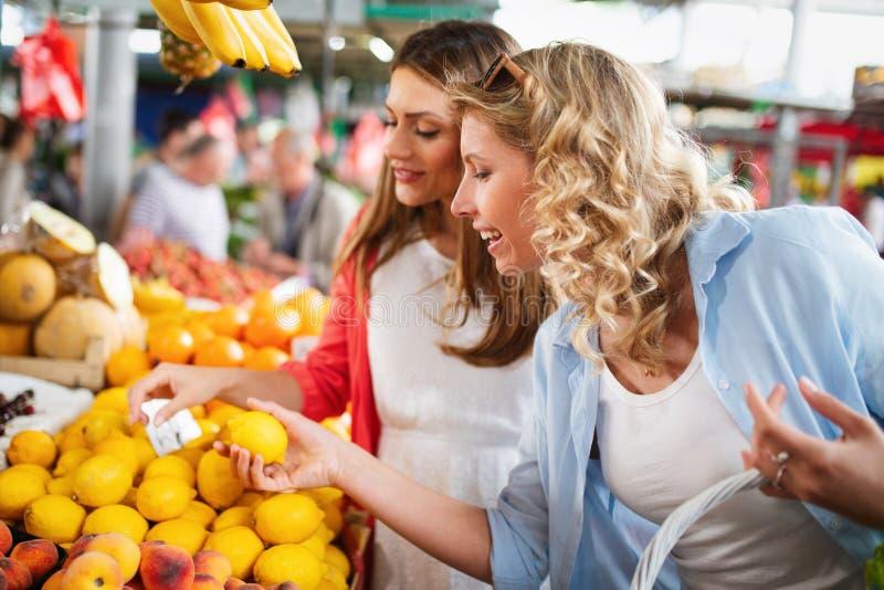 Mooie gelukkige vrouwen het winkelen groenten en vruchten stock foto