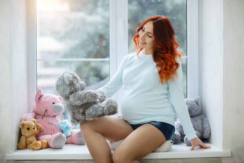 Mooie gelukkige zwangere vrouw dichtbij het venster royalty-vrije stock foto's