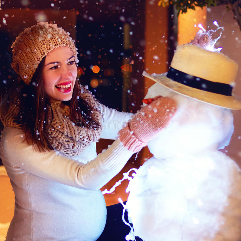 Mooie gelukkige zwangere vrouw die sneeuwman maken onder magische de wintersneeuw stock afbeelding