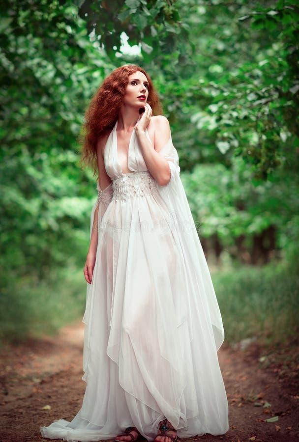 Mooie gembervrouw die witte kleding in een bosje dragen stock foto's