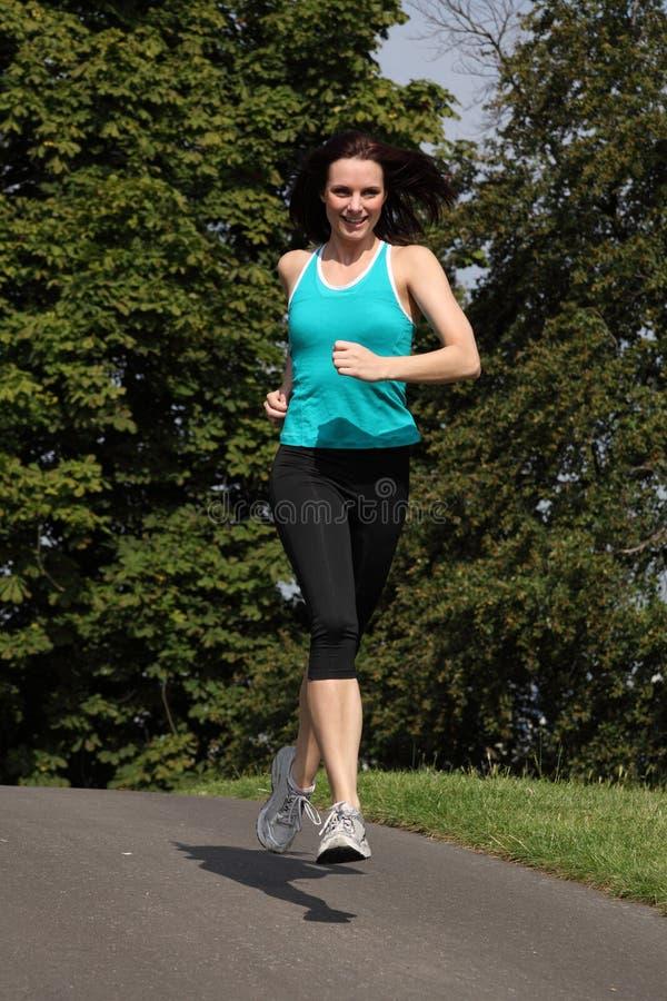 Mooie geschikte vrouw die voor oefening in park aanstoot stock afbeeldingen