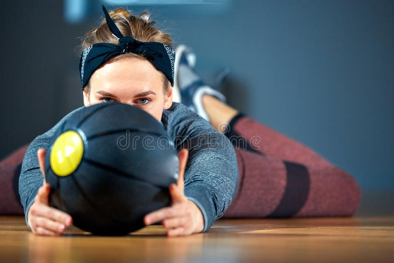 Mooie geschikte vrouw in sportkleding die terwijl het liggen op de vloer met basketbal voor venster bij gymnastiek Gezond meisje  royalty-vrije stock fotografie