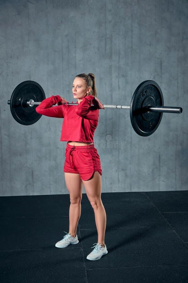 Mooie geschiktheidsvrouw die barbell opheffen Sportieve vrouw het opheffen gewichten Geschikt meisje die de bouwspieren uitoefene stock afbeelding