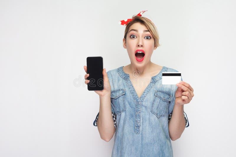 Mooie geschokte jonge vrouw in toevallig blauw denimoverhemd met make-up en rode hoofdband die, houdend creditcard en telefoon me royalty-vrije stock fotografie