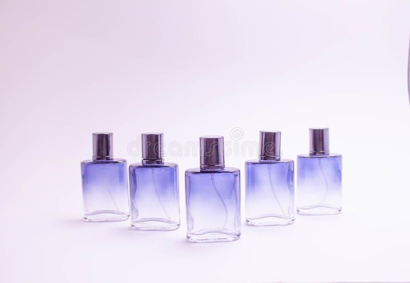 Mooie glasflessen verschillende kleuren van parfum op een witte achtergrond stock afbeeldingen