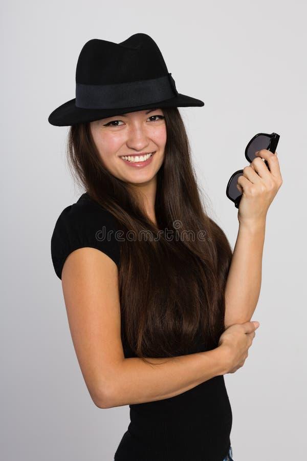 Mooie glimlachende Aziatische jonge vrouw in een vilten hoed stock afbeeldingen