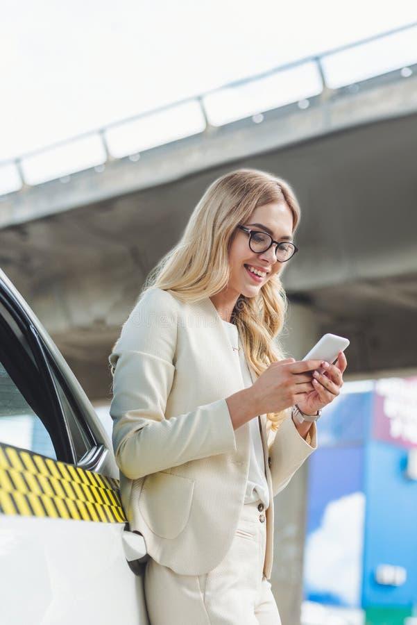 mooie glimlachende blondevrouw in oogglazen die bij taxi cabine en het gebruiken leunen stock afbeeldingen