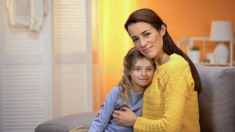 Mooie glimlachende dame die gelukkig meisje, familie koesteren die aan camera, ouderschap kijken royalty-vrije stock foto