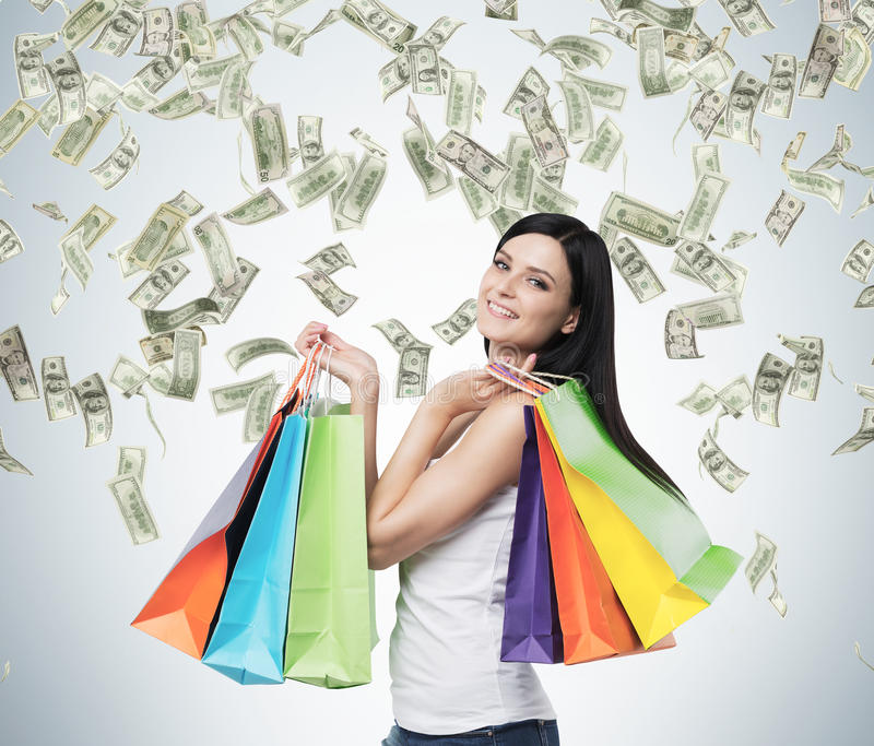 Mooie glimlachende donkerbruine vrouw met de kleurrijke het winkelen zakken van de buitensporige winkels stock afbeelding