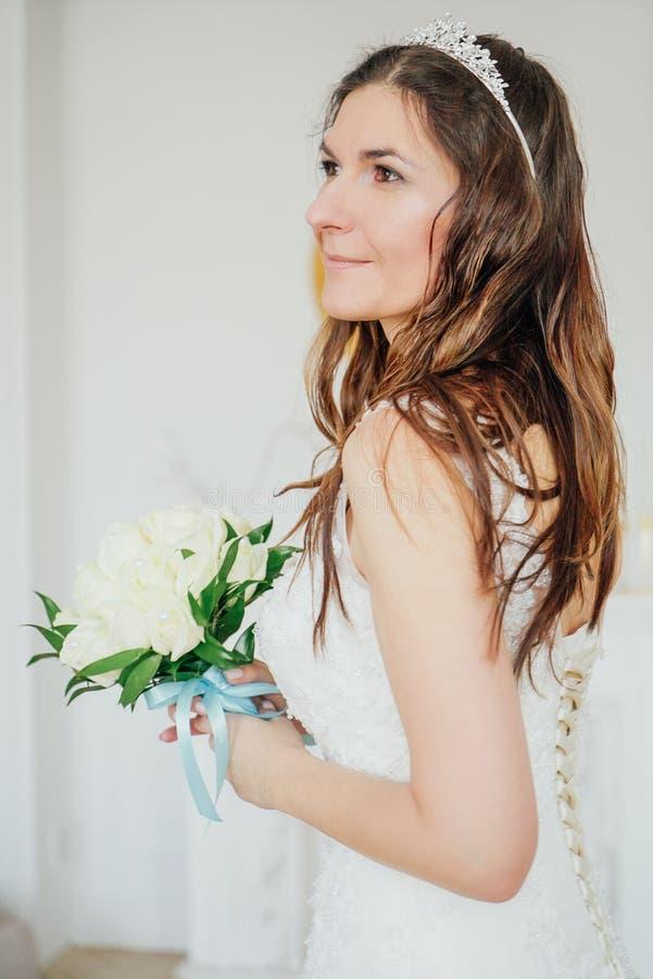 Mooie glimlachende donkerbruine vrouwenbruid in huwelijkskleding met klassiek wit rozenboeket in woonkamer stock afbeelding