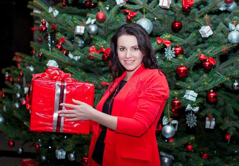 Mooie glimlachende jonge donkerbruine vrouw, die zich dichtbij Kerstboom bevinden royalty-vrije stock foto