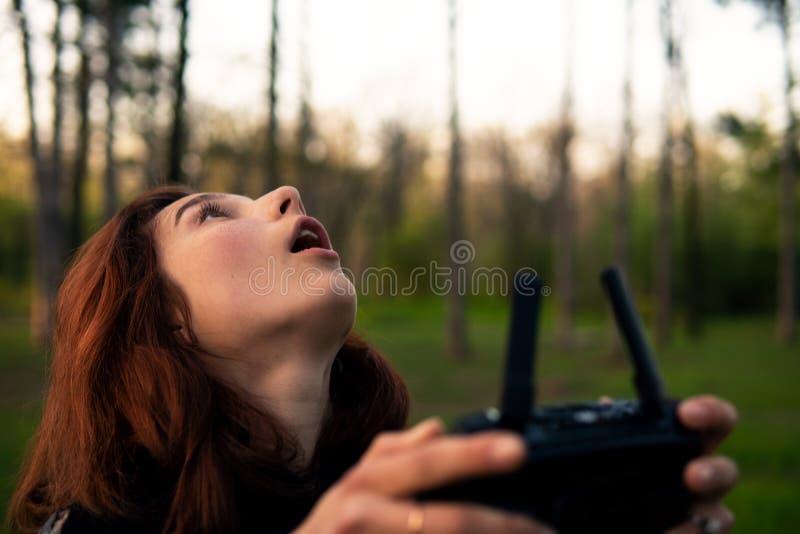 Mooie glimlachende jonge rode hoofdvrouw die hommel gebruiken enthousiaste proefmeisje het drijven Vliegende hommel met ver contr royalty-vrije stock fotografie