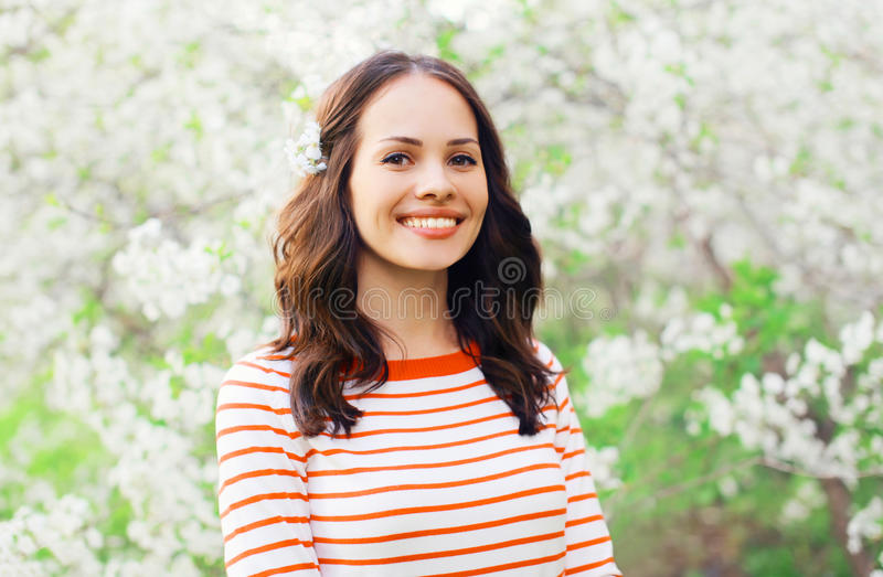 Mooie glimlachende jonge vrouw in bloeiende de lentetuin stock foto's