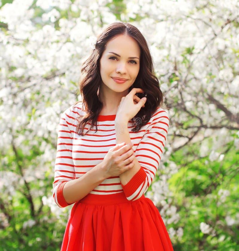 Mooie glimlachende jonge vrouw in bloeiende de lentetuin royalty-vrije stock fotografie