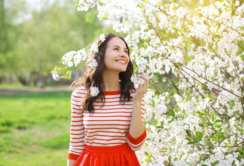 Mooie glimlachende jonge vrouw die de geur van bloeiende lente genieten royalty-vrije stock afbeeldingen