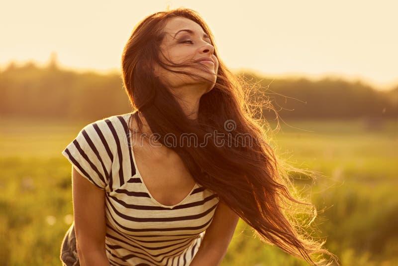 Mooie glimlachende jonge vrouw die gelukkig met lang verbazend helder lang haar op de zomerachtergrond van de aard heldere zonson royalty-vrije stock foto