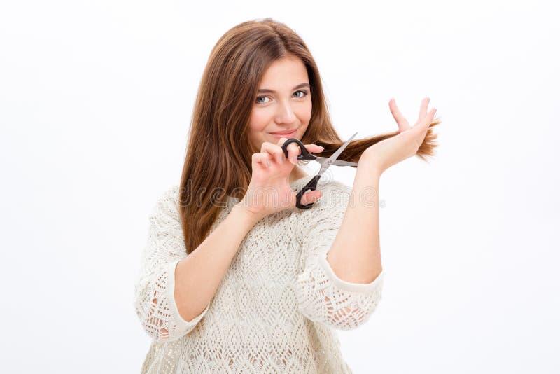 Mooie glimlachende jonge vrouw die haar haar snijden stock fotografie